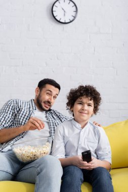 Frightened arabian man eating popcorn while watching tv with son at home stock vector