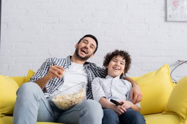 Laughing muslim man eating popcorn while watching film with son at home stock vector