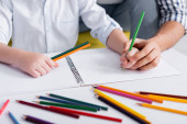 cropped view of man helping kid drawing with pencil on blurred foreground