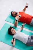 Vysoký úhel pohledu arabského syna trénink s činkami v blízkosti otce na fitness mat