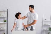 Fröhlich arabischer Vater umarmt Sohn im Badezimmer