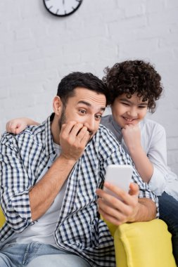 Excited arabian dad and son looking at mobile phone at home stock vector