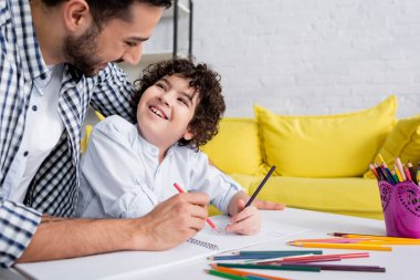 Joyful muslim kid and father looking at each other while drawing with pencils together stock vector