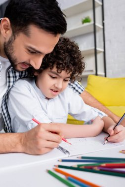 Happy arabian dad and son drawing with pencils in sketchbook together on blurred foreground stock vector