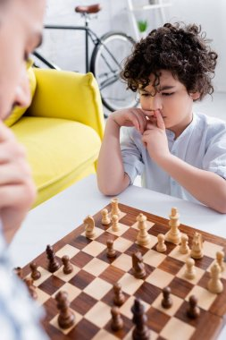 Pensive arabian boy playing chess near father on blurred foreground stock vector