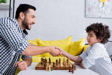 Smiling arabian father and child handshaking near chess stock vector