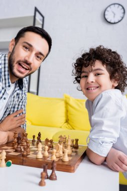 Happy muslim father and child looking at camera near chess on blurred foreground stock vector