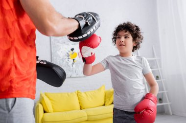 Father in punch mitts standing near muslim son in boxing gloves at home stock vector