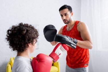 Arabian man in punch mitts training with son in boxing gloves on blurred foreground stock vector