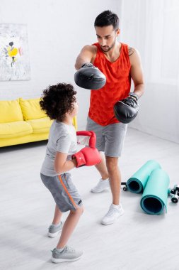 Muslim father and son boxing near sport equipment at home stock vector