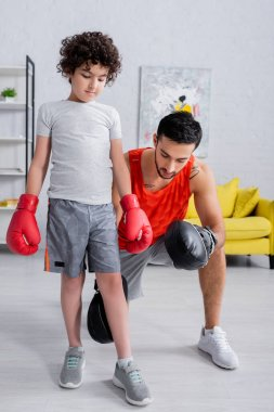Arabian man in punch mitts teaching son in boxing gloves during work out at home stock vector