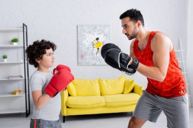 Muslim son in boxing gloves exercising with father at home stock vector