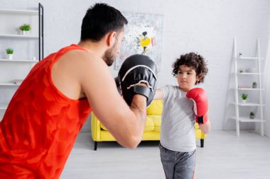Arabian boy boxing with father on blurred foreground in living room stock vector
