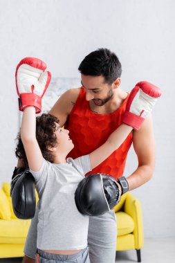 Arabian man standing near cheerful son in boxing gloves at home stock vector