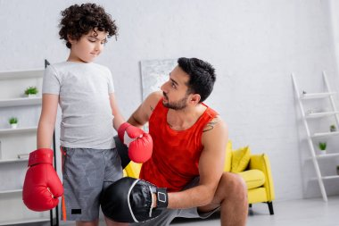 Muslim man in punch mitts standing near son in boxing gloves in living room stock vector