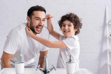 Cheerful arabian boy holding tweezers near eyebrow of father in bathroom stock vector