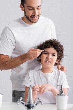 Smiling arabian man holding tweezers near eyebrow of confused son in bathroom stock vector