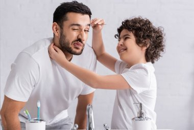 Smiling muslim boy pulling out eyebrow of father in bathroom stock vector