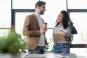 Lächelnde multiethnische Geschäftsleute mit Coffee to go und Papieren im Büro
