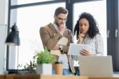 Pessimistische Geschäftsleute blicken auf digitales Tablet in der Nähe von Laptop und Kaffee, um unscharf in den Vordergrund zu treten