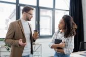 Podnikatel drží kávu při rozhovoru s africkým americkým kolegou s notebookem