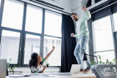 Cheerful african american businesswoman showing yes gesture while colleague dancing in office