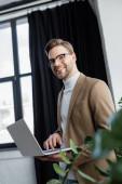 Mosolygó üzletember szemüvegben laptopot használ növény közelében elmosódott előtérben