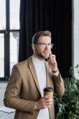 fiatal üzletember beszél a mobiltelefon, miközben a kezében kávéscsésze az irodában