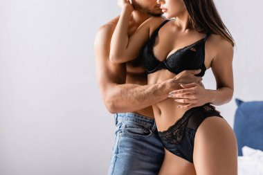 Cropped view of passionate woman in lace lingerie hugging boyfriend in bedroom
