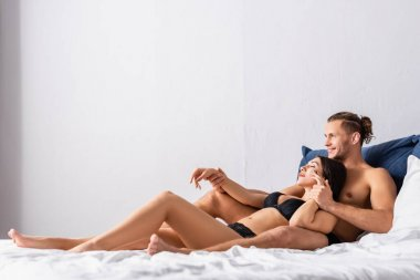Smiling man lying near sexy girlfriend in black lingerie on bed stock vector