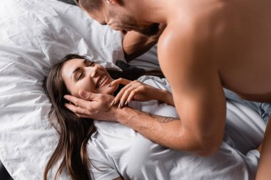 High angle view of smiling man touching face of pretty girlfriend in t-shirt on bed stock vector