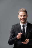 radostný podnikatel držící mobilní telefon s prázdnou obrazovkou izolovanou na šedé