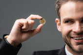 oříznutý pohled na radostného podnikatele ukazujícího mince izolované na šedé