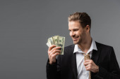 happy businessman with tie made of rope holding dollar banknotes isolated on grey