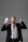 radostný podnikatel s provazem na krku drží peníze a ukazuje palec nahoru izolované na šedé