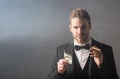 elegáns üzletember kezében égett dollár bankjegy és szivar szürke alapon füst
