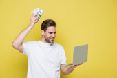 happy man holding dollars and laptop on yellow
