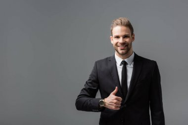 Happy businessman in black suit showing like while smiling at camera isolated on grey stock vector