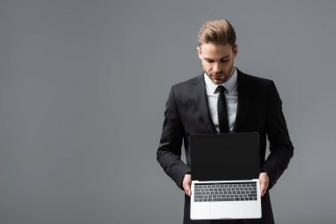 Young businessman in black suit holding laptop with blank screen isolated on grey stock vector