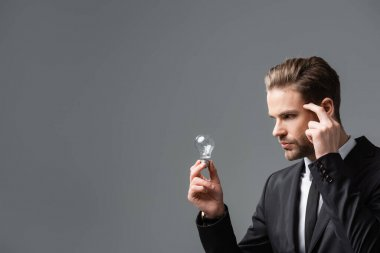 Pensive businessman touching head while looking at light bulb isolated on grey stock vector