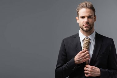 frustrated businessman looking at camera and touching tie made of rope isolated on grey