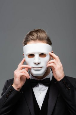 Young businessman hiding face with mask isolated on grey stock vector