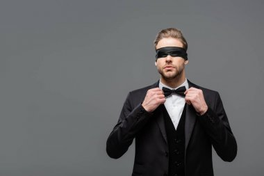 Elegant, blindfolded businessman adjusting bow tie isolated on grey stock vector