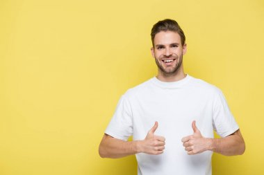 Pleased man smiling at camera and showing thumbs up on yellow stock vector