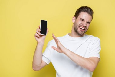 man feeling disgust and showing refuse gesture while holding cellphone with blank screen on yellow