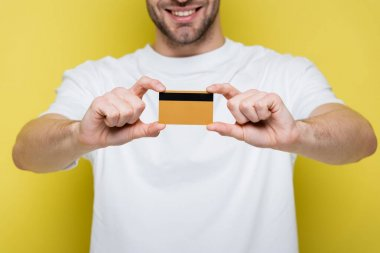 Cropped view of smiling man showing credit card on yellow, blurred background stock vector