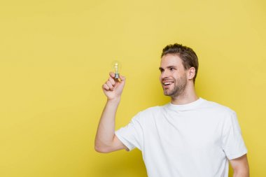 Cheerful man looking at light bulb on yellow stock vector