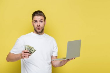 Astonished man with laptop and dollar banknotes looking at camera on yellow stock vector