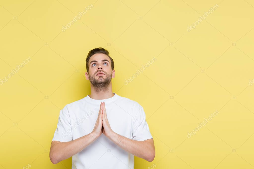 Young man looking up while showing hope gesture on yellow stock vector