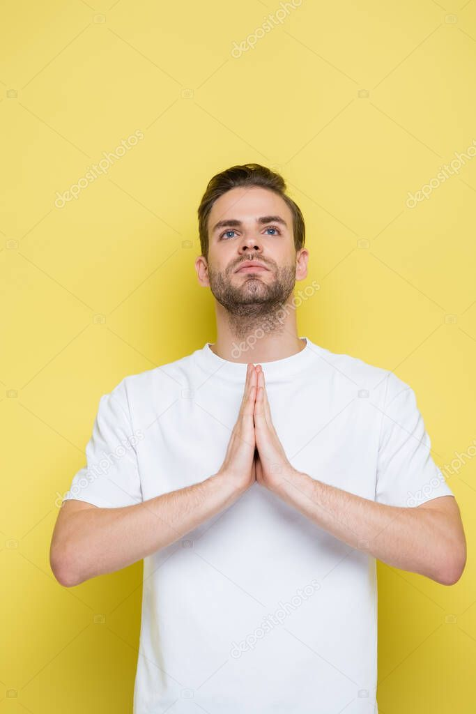 Young man looking up while standing with praying hands on yellow stock vector
